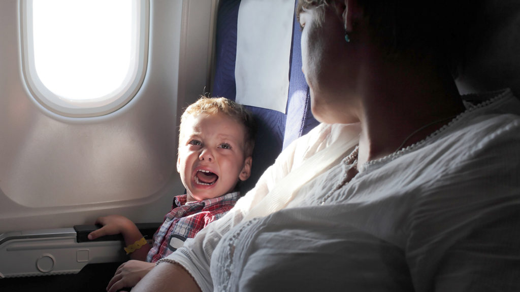 A crying toddler with parent on airplane